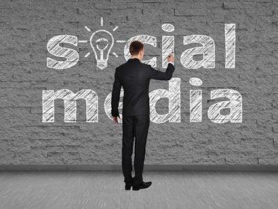 businessman drawing social media on brick wall